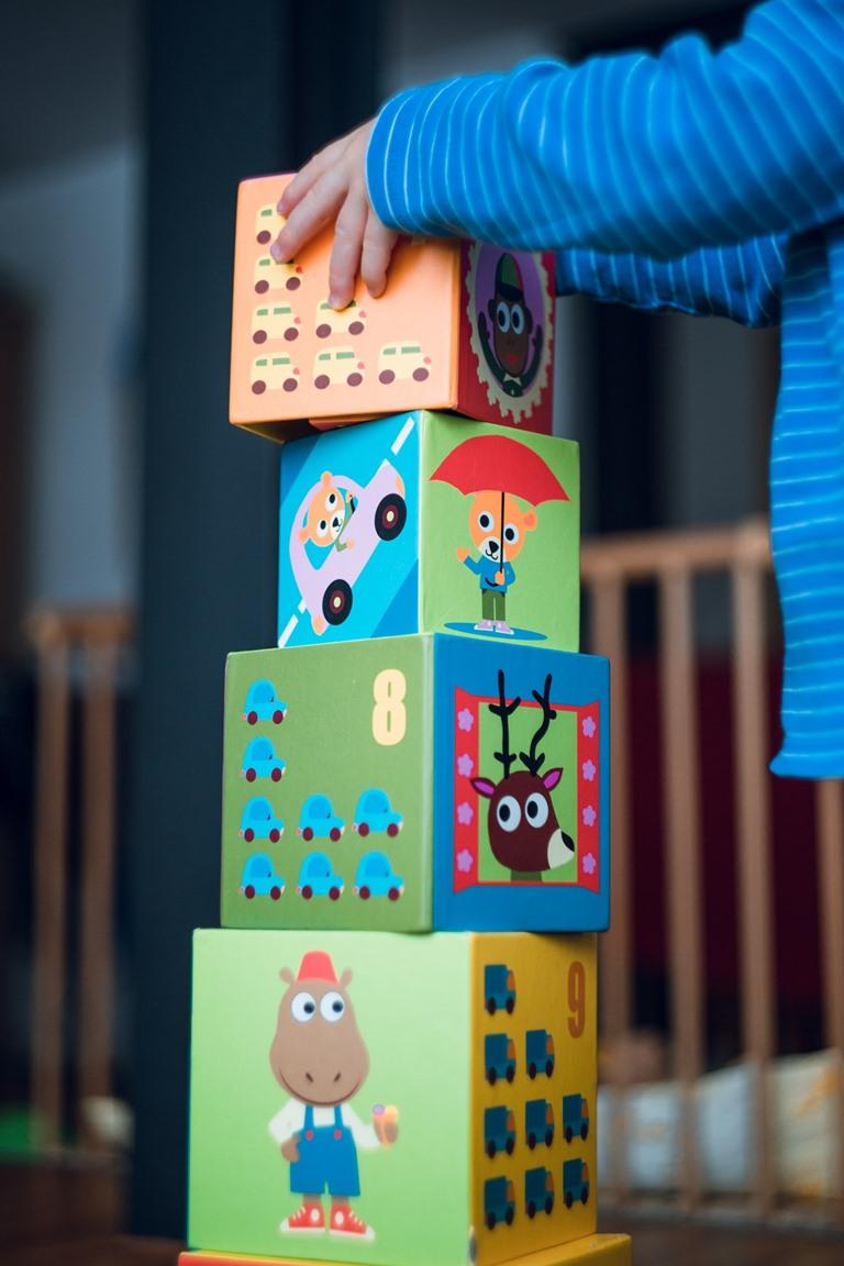 کودک در حال قرار دادن بلوک های مقوایی بر روی هم